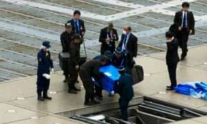 Officials carry a blue box that local media reported contains a drone from the rooftop of Shinzo Abe's offices in Tokyo.