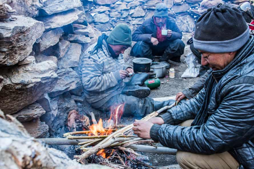 The porters take a break to cook food over an open fire.