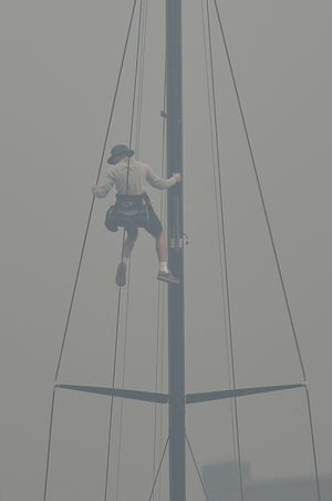 A sailor climbs the mast of a yacht enveloped in haze caused by nearby bushfires at the Cruising Yacht Club of Australia