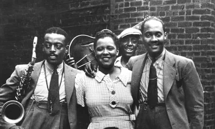 Ben Webster, Billie Holiday, unknown guitar player and Johnny Russell pose in Harlem in 1935.