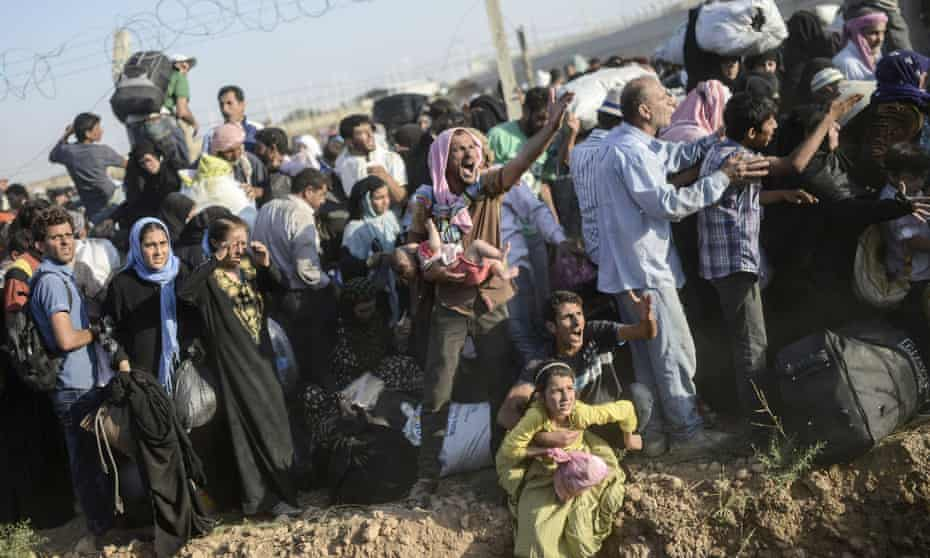 Syrians fleeing the war pass through border fences and trenches to enter Turkey illegally, near the Turkish border crossing at Akçakale in Şanlıurfa province on 14 June 2015.<br>