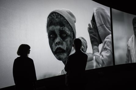 Visitors watch Richard Mosse's Incoming in the Barbican's Curve gallery.