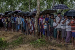 Rohingya Muslim men, who crossed over from Myanmar into Bangladesh, wait for their turn to collect a bag of rice distributed by aid agencies in Balukhali refugee camp, Bangladesh