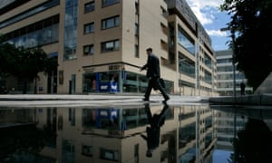 A businessman avoids puddles at the International Financial Services Centre in Dublin's business district.