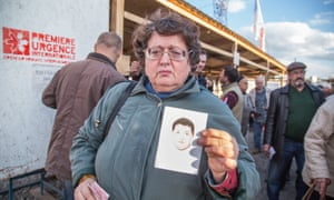 At the Mayorsk crossing point, Tatiana Chevchenko holds up a photograph of her son, Egor, who has  disappeared.