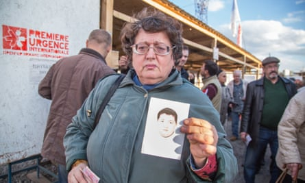 At the Mayorsk crossing point, Tatiana Chevchenko holds up a ­photograph of her son, Egor, who has  disappeared.