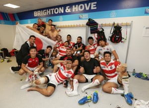 Japan players celebrate in the dressing room following victory