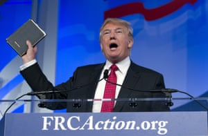 Donald Trump holds up his bible as he speaks during the Values Voter Summit in Washington.