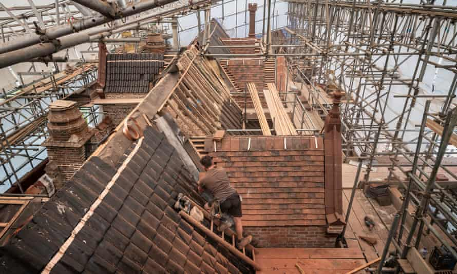 New tiles being fitted to the roof of the 15th-century moated manor house