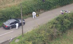 Forensic investigators examine a car at the scene.