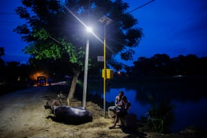 A man and child sit under a light powered from a solar microgrid at night in the village of Dharnai in Jehanabad