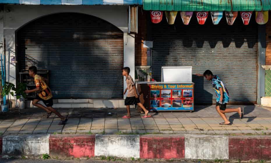 Children run past closed shops along Phuket's Karon Beach
