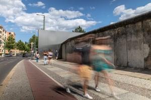 Pedestrians walk alongside a remaining section of wall