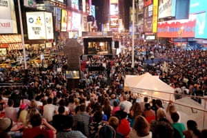 Thousands gather in Times Square to watch a screening of the season four premiere of Mad Men, the Emmy award-winning US drama set in the world of advertising in 1960s New York.