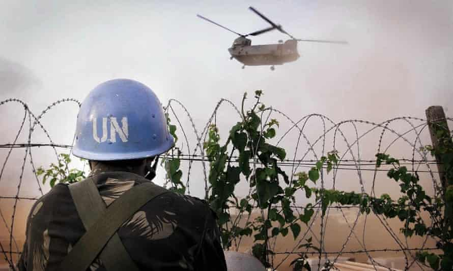 An Indian UN soldier watches an RAF Chinook helicopter