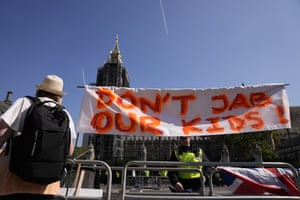 A banner against giving children the Covid vaccine on display during a protest in Parliament Square today.