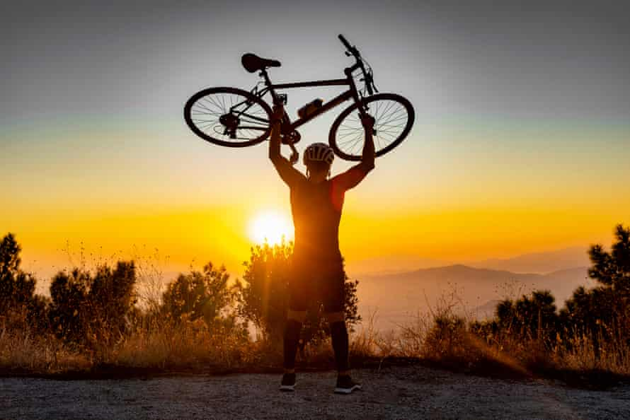 Male biker holds bike above head after successfully biking up a hill at sunset