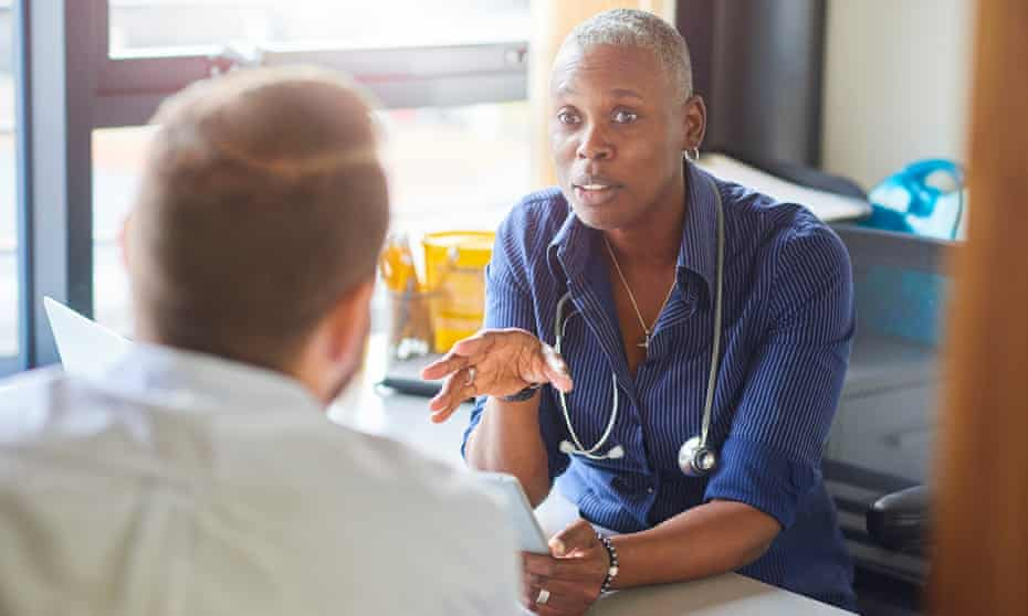 A doctor sits at her desk and chats to a patient.