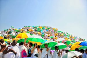 Muslim pilgrims, carrying umbrellas to block the sun, gather on Mount Arafat on the eve of Eid al-Adha.