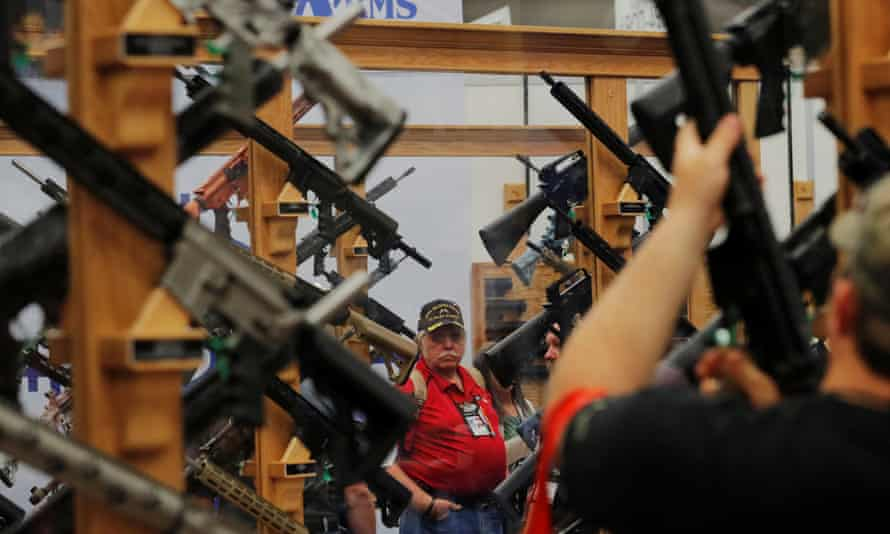Gun enthusiasts look at rifles during the annual National Rifle Association (NRA) convention in Dallas, Texas, in May 2018.