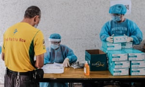 Medical workers wearing protective suits hand out test kits to local residents to collect samples for COVID-19 test at a residential block on August 7, 2020 in Hong Kong.