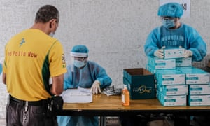 Medical workers wearing protective suits hand out test kits to local residents to collect samples for Covid-19 tests at a residential block on Friday in Hong Kong.
