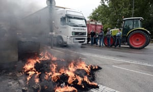 Farmers block access to vehicles as they protest on a bridge between France and Germany.