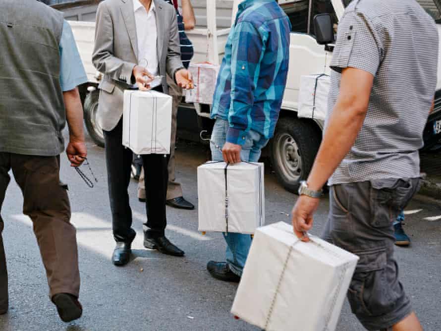 Men gather with their bird boxes.