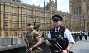 Soldiers and armed police patrol near the Houses of Parliament.