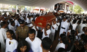 Coffins are carried to the graves during the mass funeral of the victims of series of bomb blasts, at cemetery Don David Katuwapitiya in Colombo, Sri Lanka, 23 April 2019.