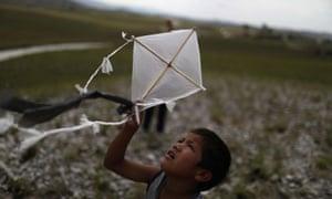 An indigenous boy of the Pemon tribe flies a kite near his village in Tarau Paru, Brazil