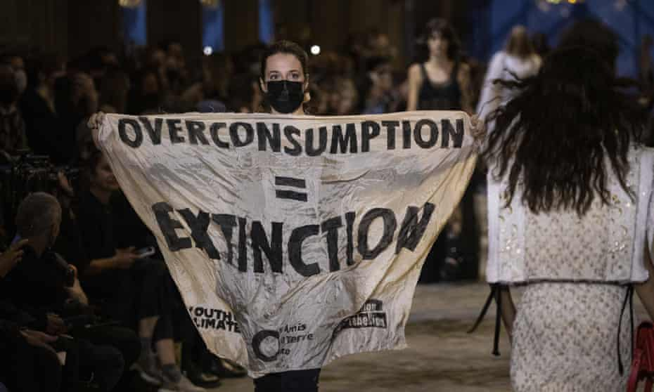 An Extinction Rebellion protester on the runway during the Louis Vuitton show in Paris holding a sign reading 'overconsumption = extinction'