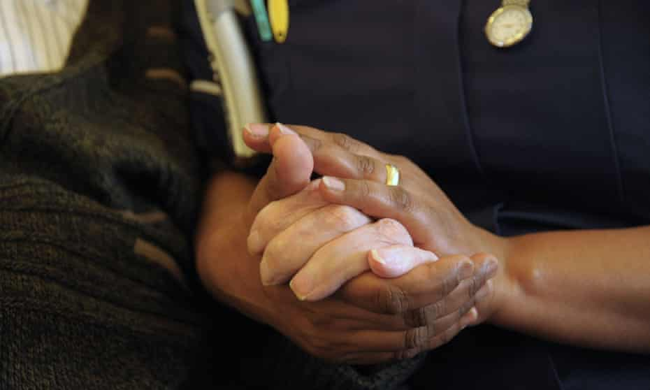 close up on hands of a white patient held by hands of a black nurse