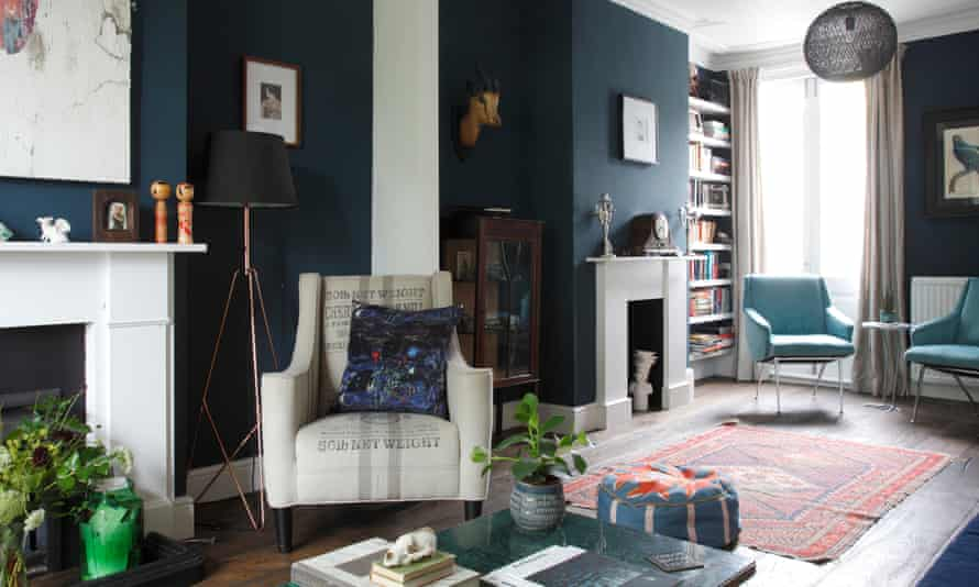 Living room with armchair, fireplaces, bookshelves, rug and dark blue walls