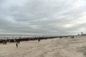 People form a human chain on the beach as part of a march against climate change in Ostend, Belgium, 6 December