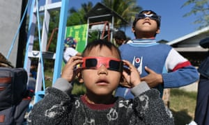 Children uses eclipse glasses to watch a rare solar eclipse central Myanmar