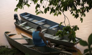 A man sits on the banks of the Rio Doce