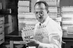 In this Oct. 7, 1954 file photo, Dr. Jonas Salk, developer of the polio vaccine, holds a rack of test tubes in his lab in Pittsburgh, PA