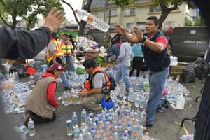 Volunteers distribute water to survivors and rescue workers