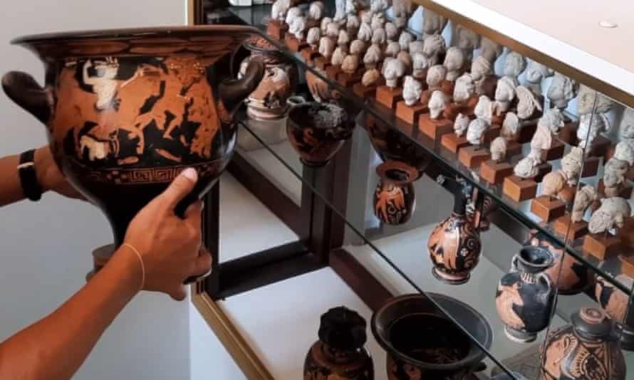 A police officer handles one of the nearly 800 archeological pieces 'of exceptional rarity and inestimable value' recovered from a Belgian collector