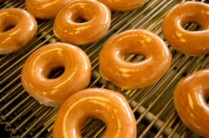 After a quick baking and frying process, Krispy Kreme Original Glazed doughnuts roll out with their famous shiny sugar coating.