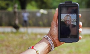 Barbara Scott, cousin of Walter Scott, holds a photo of Walter Scott on her cellphone in North Charleston, South Carolina, on 8 April 2015.