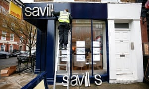 A worker puts up a Savills estate agents sign in London.