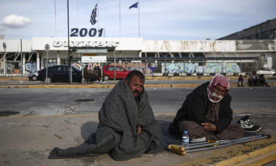 Two men from Iraq sit at a parking area outside the old international airport, which is used as a shelter for refugees and migrants, in southern Athens.