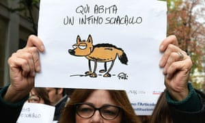 A journalist holds a placard reading 'Here lives a vulgar jackal' in a Milan protest.