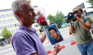 Naim Zabergja holds a photo of his son Dijamant at the Olympia shopping centre in Munich where the shooting took place