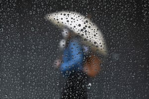 Woman with umbrella shot through rain-covered window