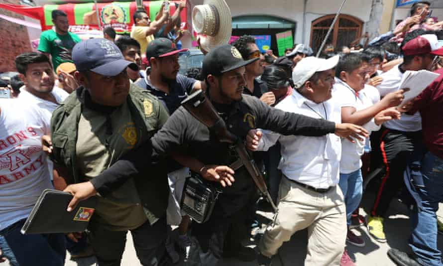 Members of the community police help to open a road as the presidential candidate Andrés Manuel López Obrador leaves a campaign rally in Guerrero state.