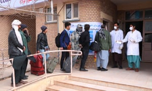 Afghan health officials screen passengers entering Afghanistan from Iran at the border in Herat