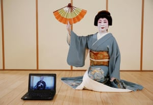 Tokijyo Hanasaki, a jiutamai dancer, poses for a photograph behind a laptop playing a musical performance which was filmed in advance in order to avoid physical contact, to accompany Hanasaki's dance performance for a film being made that is supported by the Tokyo Metropolitan government in order to support artists during the coronavirus disease
